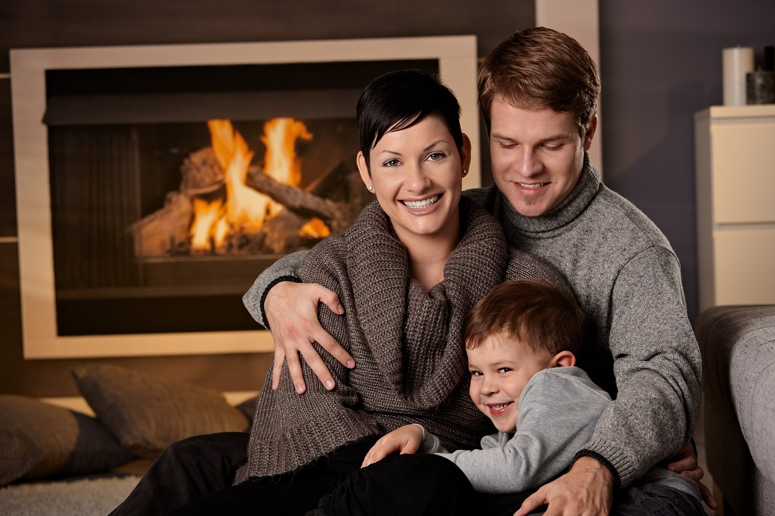 Happy family sitting on couch at home in a cold winter day looking at camera smiling.