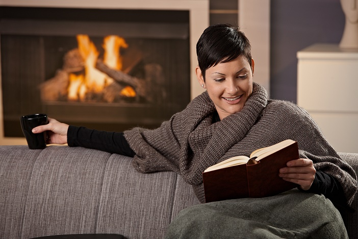 Woman sitting on sofa at home on a cold winter day reading book.