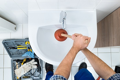 High Angle View Of Male Plumber Using Plunger In Bathroom Sink ** Note: Shallow depth of field